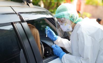 A person in their car receiving a COVID-19 test